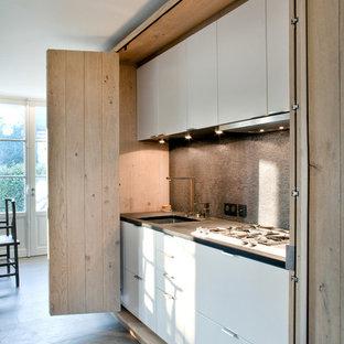 Foto de cocina de galera, bohemia, pequeña, abierta, sin isla, con fregadero bajoencimera, armarios con paneles lisos y puertas de armario blancas