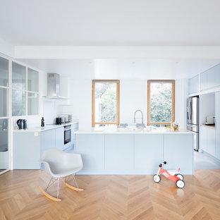 Inspiration pour une grande cuisine ouverte design en U avec un évier encastré, un placard à porte plane, des portes de placard bleues, une crédence blanche, un électroménager en acier inoxydable, un sol en bois clair, un îlot central, un plan de travail blanc, un plan de travail en stratifié et un sol gris.