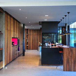 Idée de décoration pour une grand cuisine ouverte linéaire design avec des portes de placard en bois sombre, un plan de travail en bois, béton au sol et un îlot central.