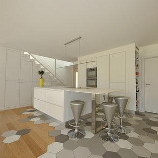 Inspiration pour une cuisine américaine parallèle design de taille moyenne avec un placard à porte affleurante, des portes de placard blanches et une péninsule.
