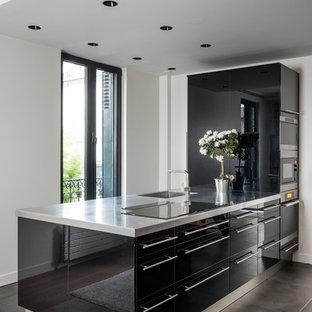 Idée de décoration pour une cuisine américaine linéaire design de taille moyenne avec béton au sol, un sol gris, un évier encastré, un placard à porte affleurante, des portes de placard en bois brun, un électroménager encastrable, un îlot central et un plan de travail gris.
