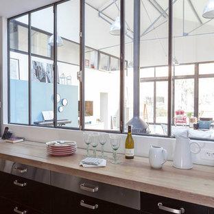 パリの大きいインダストリアルスタイルのおしゃれなキッチン (エプロンフロントシンク、インセット扉のキャビネット、黒いキャビネット、木材カウンター、白いキッチンパネル、パネルと同色の調理設備、コンクリートの床、アイランドなし、グレーの床、ベージュのキッチンカウンター) の写真