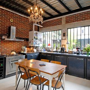 Foto di una grande cucina industriale con ante lisce, ante nere, paraspruzzi rosso e elettrodomestici in acciaio inossidabile