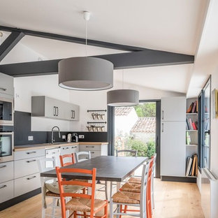 Design ideas for a contemporary l-shaped eat-in kitchen in Other with a drop-in sink, flat-panel cabinets, grey cabinets, wood benchtops, black splashback, stainless steel appliances, medium hardwood floors, brown floor and beige benchtop.