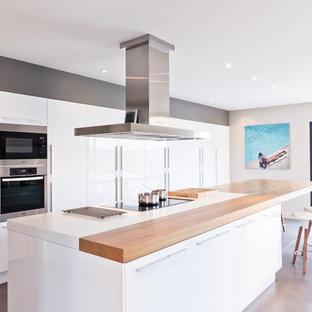 Réalisation d'une grand cuisine américaine linéaire design avec un placard à porte plane, des portes de placard blanches et un îlot central.