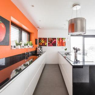 Exemple d'une cuisine ouverte parallèle tendance de taille moyenne avec un évier encastré, des portes de placard blanches, un plan de travail en granite, une crédence orange, un électroménager noir, un sol en carrelage de céramique, un sol gris, un placard à porte plane et une péninsule.