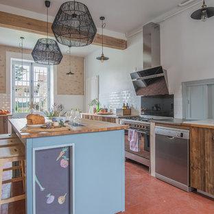 パリのカントリー風おしゃれなキッチン (ドロップインシンク、フラットパネル扉のキャビネット、中間色木目調キャビネット、木材カウンター、赤い床、茶色いキッチンカウンター) の写真