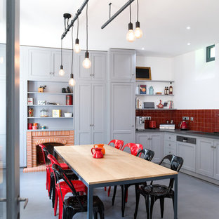 Aménagement d'une cuisine américaine contemporaine en L avec un placard à porte shaker, des portes de placard grises, une crédence rouge, béton au sol, aucun îlot et un électroménager de couleur.