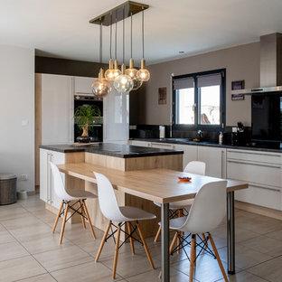 Cette image montre une cuisine américaine design en L avec un placard à porte plane, des portes de placard blanches, une crédence noire, un électroménager encastrable, un îlot central, un sol beige et un plan de travail noir.