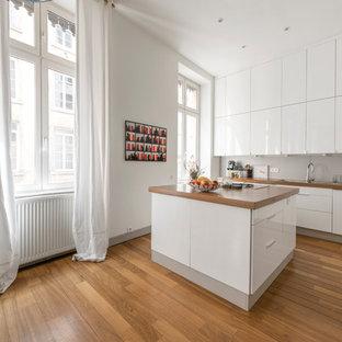 Inspiration pour une grand cuisine ouverte design en L avec des portes de placard blanches, un plan de travail en bois, une crédence grise, un électroménager encastrable, un sol en bois brun, un îlot central, un évier posé et un placard à porte plane.