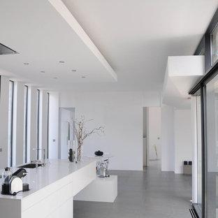 Idée de décoration pour une cuisine ouverte linéaire design de taille moyenne avec des portes de placard blanches et un îlot central.