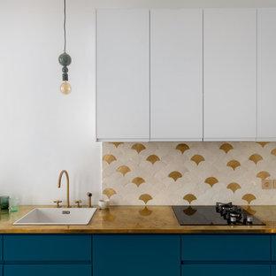 Свежая идея для дизайна: параллельная кухня-гостиная среднего размера в скандинавском стиле с одинарной раковиной, фасадами с декоративным кантом, синими фасадами, столешницей из меди, белым фартуком, фартуком из керамической плитки, черной техникой, светлым паркетным полом, коричневым полом и желтой столешницей без острова - отличное фото интерьера