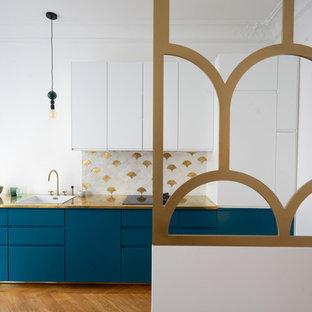 Неиссякаемый источник вдохновения для домашнего уюта: параллельная кухня-гостиная среднего размера в скандинавском стиле с одинарной раковиной, фасадами с декоративным кантом, синими фасадами, столешницей из меди, белым фартуком, фартуком из керамической плитки, черной техникой, светлым паркетным полом, коричневым полом и желтой столешницей без острова