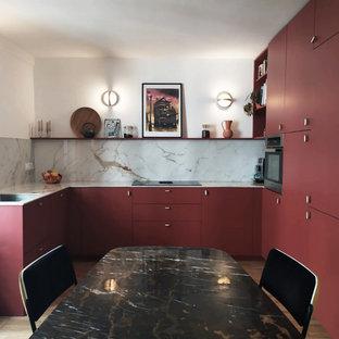 Cette image montre une cuisine design en U de taille moyenne avec un évier encastré, un placard à porte plane, des portes de placard rouges, une crédence grise, un électroménager encastrable, un sol marron et un plan de travail gris.