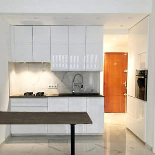 Design ideas for a small contemporary galley open plan kitchen in Nice with a single-bowl sink, beaded inset cabinets, white cabinets, laminate benchtops, white splashback, marble splashback, stainless steel appliances, marble floors, with island, white floor and brown benchtop.