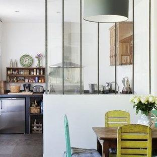 ボルドーの中くらいのカントリー風おしゃれなキッチン (アンダーカウンターシンク、フラットパネル扉のキャビネット、淡色木目調キャビネット、木材カウンター、セメントタイルのキッチンパネル、白い調理設備、テラコッタタイルの床、赤い床) の写真