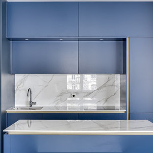 Contemporary kitchen pictures - Inspiration for a contemporary single-wall kitchen remodel in Paris with an undermount sink, flat-panel cabinets, blue cabinets, gray backsplash, an island and gray countertops