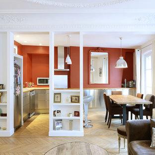 Inspiration pour une cuisine américaine design en L de taille moyenne avec un sol en bois clair, un évier posé, un placard à porte plane, une façade en inox, un plan de travail en bois, une crédence rouge, un électroménager en acier inoxydable et un îlot central.