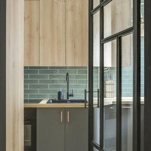 Inspiration för ett avskilt, litet industriellt brun linjärt brunt kök, med en enkel diskho, luckor med profilerade fronter, skåp i ljust trä, träbänkskiva, grönt stänkskydd, stänkskydd i tunnelbanekakel, integrerade vitvaror, cementgolv och grönt golv