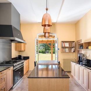 Idée de décoration pour une grande cuisine méditerranéenne avec des portes de placard en bois clair, un plan de travail en granite, un sol en travertin, un îlot central, un plan de travail noir, un placard à porte shaker, une crédence métallisée, un électroménager noir et un sol beige.