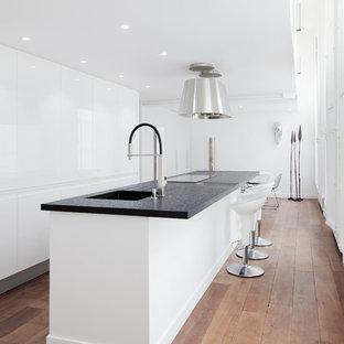 Esempio di una cucina contemporanea di medie dimensioni con lavello sottopiano, ante lisce, ante bianche, elettrodomestici da incasso, pavimento in legno massello medio e isola