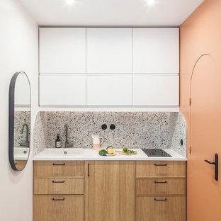 Идея дизайна: маленькая линейная кухня-гостиная в стиле модернизм с одинарной раковиной, фасадами с декоративным кантом, светлыми деревянными фасадами, столешницей из ламината, разноцветным фартуком, фартуком из керамической плитки, техникой под мебельный фасад, полом из терраццо, разноцветным полом и белой столешницей