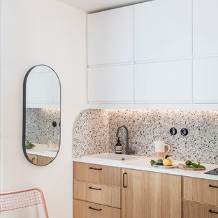 This is an example of a small modern single-wall open plan kitchen in Paris with a single-bowl sink, beaded inset cabinets, light wood cabinets, laminate benchtops, multi-coloured splashback, ceramic splashback, panelled appliances, terrazzo floors, multi-coloured floor and white benchtop.