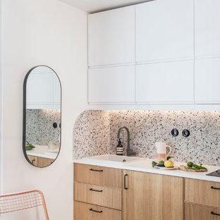На фото: маленькая линейная кухня-гостиная в стиле модернизм с одинарной раковиной, фасадами с декоративным кантом, светлыми деревянными фасадами, столешницей из ламината, разноцветным фартуком, фартуком из керамической плитки, техникой под мебельный фасад, полом из терраццо, разноцветным полом и белой столешницей с