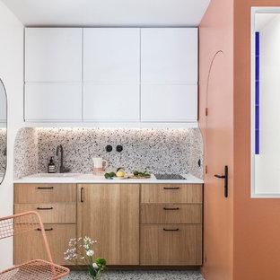Esempio di una piccola cucina minimalista con lavello a vasca singola, ante a filo, ante in legno chiaro, top in laminato, paraspruzzi multicolore, paraspruzzi con piastrelle in ceramica, elettrodomestici da incasso, pavimento alla veneziana, pavimento multicolore e top bianco