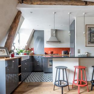 パリの地中海スタイルのおしゃれなキッチン (エプロンフロントシンク、フラットパネル扉のキャビネット、グレーのキャビネット、赤いキッチンパネル、シルバーの調理設備の、淡色無垢フローリング、ベージュの床、黄色いキッチンカウンター) の写真