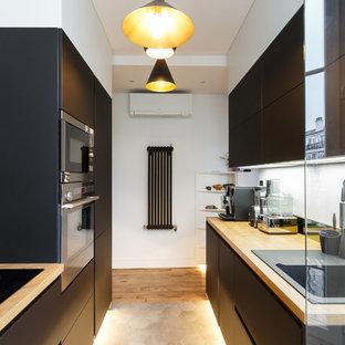 Inspiration pour une cuisine parallèle design avec un évier posé, un placard à porte plane, des portes de placard noires, un plan de travail en bois, une crédence noire, un électroménager noir, un sol en bois brun, un sol marron et un plan de travail beige.