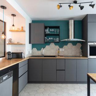 Idée de décoration pour une cuisine américaine design en L avec un évier posé, un placard à porte plane, des portes de placard grises, un plan de travail en bois, un électroménager en acier inoxydable, aucun îlot, un sol gris et un plan de travail marron.