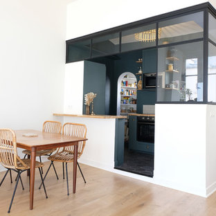 This is an example of a l-shaped open plan kitchen in Paris with a single-bowl sink, green cabinets, wood benchtops, beige splashback, terra-cotta splashback, stainless steel appliances, ceramic floors, with island, black floor and beige benchtop.
