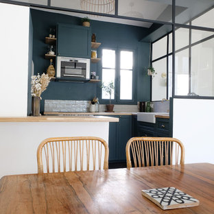 This is an example of a mid-sized industrial l-shaped open plan kitchen in Paris with a single-bowl sink, green cabinets, wood benchtops, beige splashback, terra-cotta splashback, stainless steel appliances, ceramic floors, with island, black floor and beige benchtop.