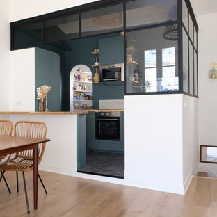 This is an example of a contemporary u-shaped eat-in kitchen in Paris with green cabinets, wood benchtops, stainless steel appliances, ceramic floors, black floor, shaker cabinets, white splashback, subway tile splashback, a peninsula and brown benchtop.
