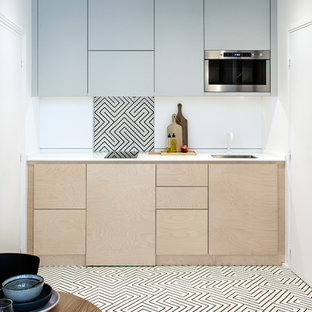 Foto di una piccola cucina scandinava con lavello sottopiano, ante lisce, ante in legno chiaro, paraspruzzi bianco, pavimento in legno massello medio, nessuna isola e pavimento marrone