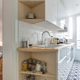 This is an example of a small scandinavian l-shaped separate kitchen in Paris with a drop-in sink, flat-panel cabinets, white cabinets, wood benchtops, white splashback, porcelain splashback, stainless steel appliances, cement tiles, no island, multi-coloured floor and beige benchtop.