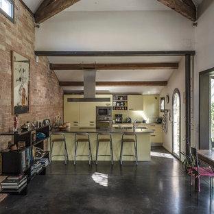 Réalisation d'une grande cuisine ouverte parallèle champêtre avec des portes de placard jaunes et une péninsule.