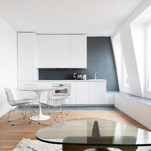 Idées déco pour une petit cuisine ouverte linéaire contemporaine avec un placard à porte plane, des portes de placard blanches, une crédence noire, une crédence en mosaïque, un électroménager en acier inoxydable, un sol en bois clair, un évier encastré et aucun îlot.