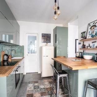 Cette image montre une cuisine linéaire design fermée avec un évier posé, un placard à porte plane, des portes de placard bleues, un plan de travail en bois, une crédence bleue, un sol multicolore, un plan de travail marron et une péninsule.