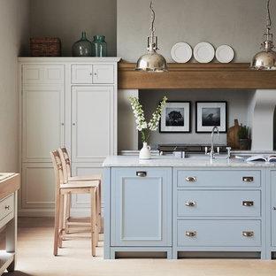 Exemple d'une cuisine parallèle chic avec un placard avec porte à panneau encastré, des portes de placard blanches, un sol en bois clair, un îlot central, un sol beige et un plan de travail blanc.