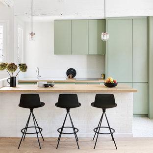 Imagen de cocina de galera, actual, con fregadero encastrado, armarios con paneles lisos, puertas de armario verdes, encimera de madera, península, suelo blanco y encimeras beige
