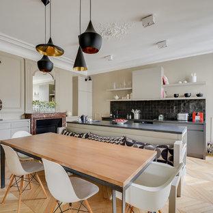 Foto di una cucina design con paraspruzzi nero, parquet chiaro, ante lisce, ante nere, top in granito e paraspruzzi con piastrelle in pietra