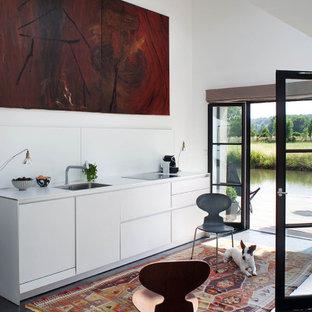 Idées déco pour une cuisine ouverte linéaire contemporaine avec des portes de placard blanches, une crédence blanche, un sol en ardoise, un sol noir, un plan de travail blanc, un évier encastré, un placard à porte plane, aucun îlot et un plafond voûté.