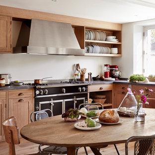 Cette photo montre une cuisine américaine nature en L de taille moyenne avec un placard à porte shaker, des portes de placard en bois brun, un électroménager noir, aucun îlot, une crédence blanche et un sol en bois brun.
