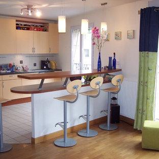 Mittelgroße Moderne Wohnküche in L-Form mit Doppelwaschbecken, Kassettenfronten, orangefarbenen Schränken, Granit-Arbeitsplatte, Küchenrückwand in Weiß, Rückwand aus Keramikfliesen, Küchengeräten aus Edelstahl, Keramikboden, Kücheninsel und weißem Boden in Paris