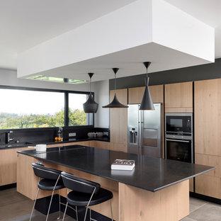 Inspiration pour une cuisine design en L avec un placard à porte plane, des portes de placard en bois clair, un électroménager en acier inoxydable, un îlot central et un sol gris.