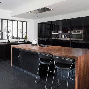 На фото: кухни в современном стиле с врезной раковиной, плоскими фасадами, черными фасадами, деревянной столешницей, фартуком с окном, техникой из нержавеющей стали, островом и черным полом