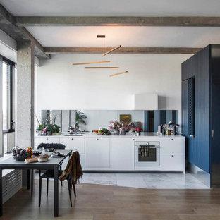 Réalisation d'une cuisine linéaire design avec un évier encastré, un placard à porte plane, des portes de placard blanches, une crédence métallisée, une crédence en carreau de miroir, un électroménager blanc, un sol en bois brun, un sol marron et un plan de travail blanc.
