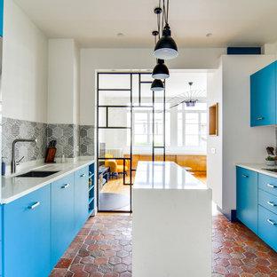 Inspiration pour une cuisine parallèle design fermée avec un évier encastré, un placard à porte plane, des portes de placard bleues, une crédence verte, un sol en brique, un îlot central, un sol rouge et un plan de travail blanc.